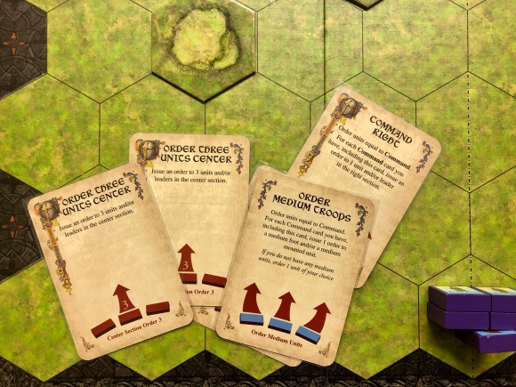 A hand of command cards from C&C Medieval on the game board